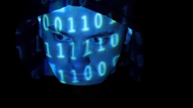 フード付きハッカーに取り組んでいる、コンピューター、バイナリーコード一風に彼の顔。ソースコード凸形を攻撃、怒っている男性の顔、黒の背景ます。 ビデオ
