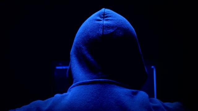 暗闇の中でコンピューターに取り組んでいるフード付きのハッカー - なりすまし犯罪点の映像素材/bロール