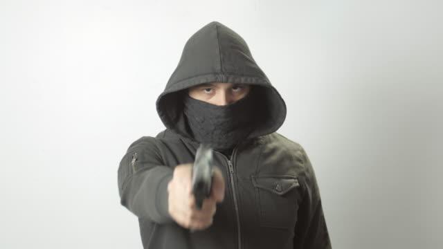 Hooded Masked Man Points Handgun at Camera video