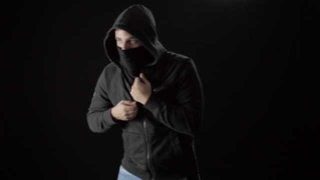 Hooded Masked Man Pulls an Assault Rifle Out of His Sweatshirt video