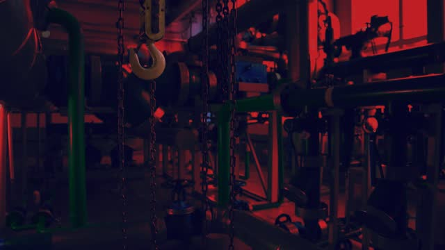 Hook and chains hang inside the factory at night