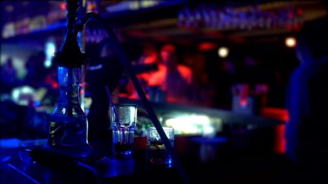水ギセルとバーの夜のクラブ、パーティーの雰囲気でカウンターに立っている 2 つのメガネ ビデオ