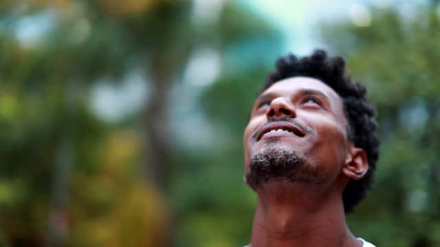 hoppfull afroamerikansk person som ser till himlen med tro och kontemplation, man firar livet - tacksamhet bildbanksvideor och videomaterial från bakom kulisserna