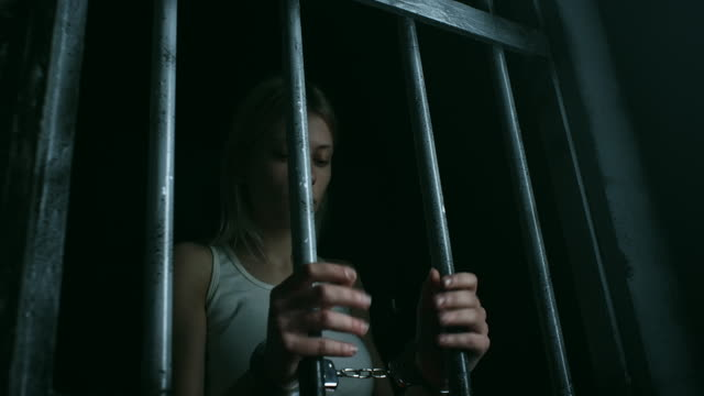 Hopeless women with handcuffs holding bars and looking through video