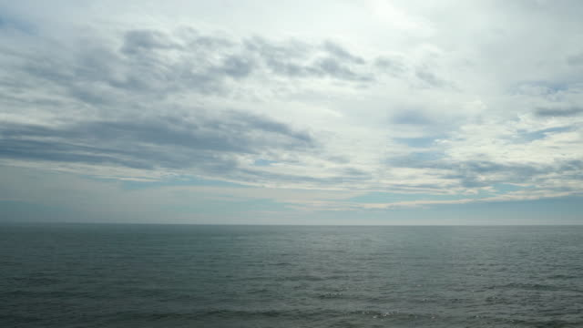 vídeos de stock e filmes b-roll de horizon over water with overcast sky - linha do horizonte sobre água