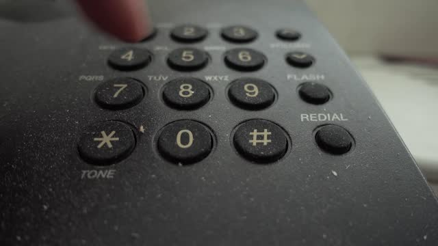 Horizontal close up video of male hand dialing number on an old landline phone.