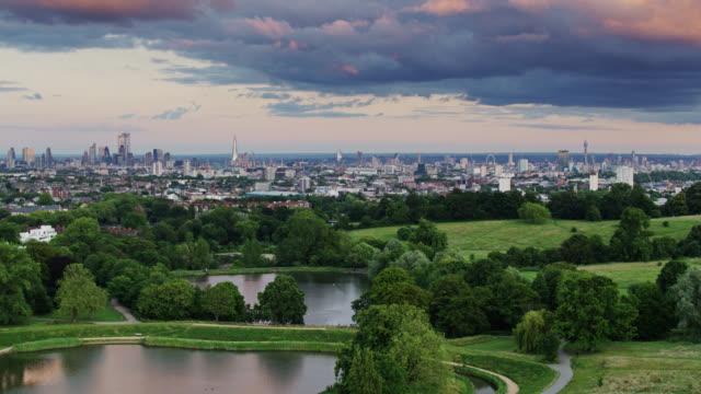 Drone horizontal tiré des champs et des étangs de Hampstead Heath avec l'horizon de Londres dans la distance - Vidéo