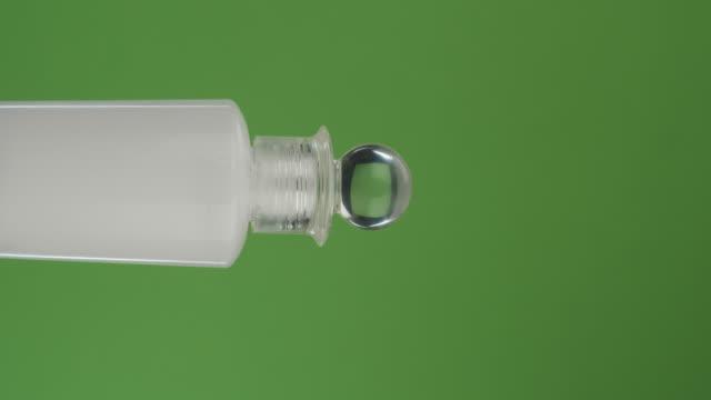 Rotation horizontale d'une bouteille de crème pour le visage sur un écran vert. Gros plan. - Vidéo