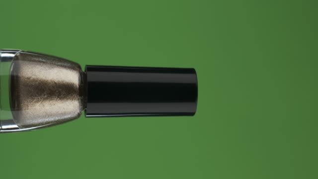 Rotation horizontale d'une bouteille en verre avec vernis à ongles, sur un écran vert. Gros plan. - Vidéo