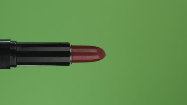 Rotation horizontale d'un rouge à lèvres rouge ouvert, sur un écran vert. Gros plan. - Vidéo