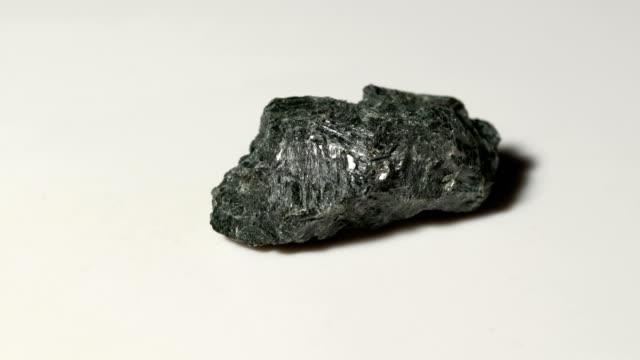 vídeos y material grabado en eventos de stock de muestra mineral hornblenda en rotación con fondo blanco - basalto