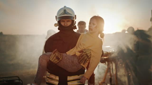 Schreckliche Szene des Autounfalls Verkehrsunfall: Mutiger Feuerwehrmann bringt verletztes junges Mädchen in Sicherheit. Im Hintergrund retten mutige Sanitäter und Feuerwehrleute Leben, bekämpfen Feuer und Rauch – Video