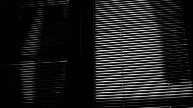 Horror scene of moving laundry shades on venetian blinds at night