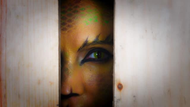 4k horror serpent makeup woman looking through hole - ветхий завет стоковые видео и кадры b-roll