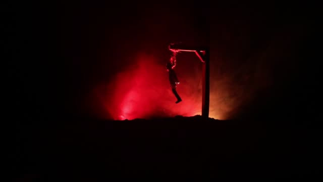 Horror view silhouette of hanged man on scaffold at night with fog and toned light on background. Execution (or suicide) decoration. Horror Halloween concept.