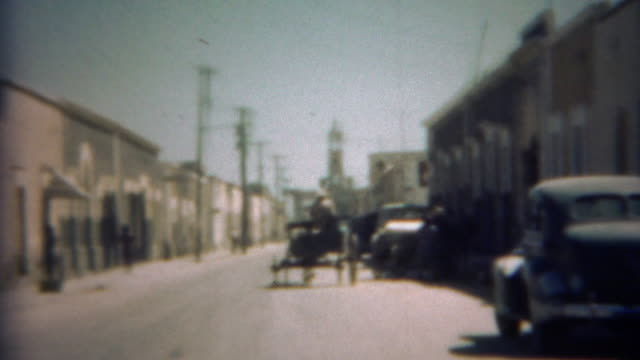 1948: Horse pulling farmers carriage crossing through urban streets.