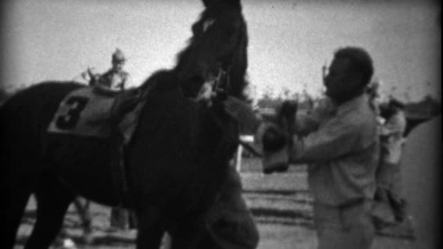 1935: horse race jockey dismounts after the race as handlers take control. - horse racing filmów i materiałów b-roll