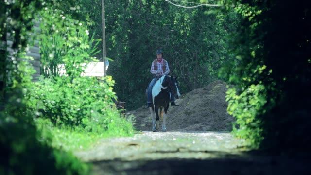 vidéos et rushes de cavalier de cheval sur le ranch se trouve sur le chemin - dressage équestre
