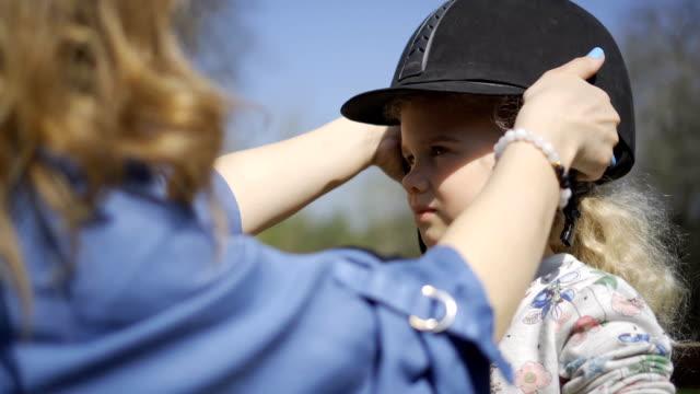 horse riding girl child helmet. gimbal motion shot - sella video stock e b–roll