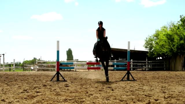 horse woman jumps through the barrier on horseback slow motion - siodło filmów i materiałów b-roll
