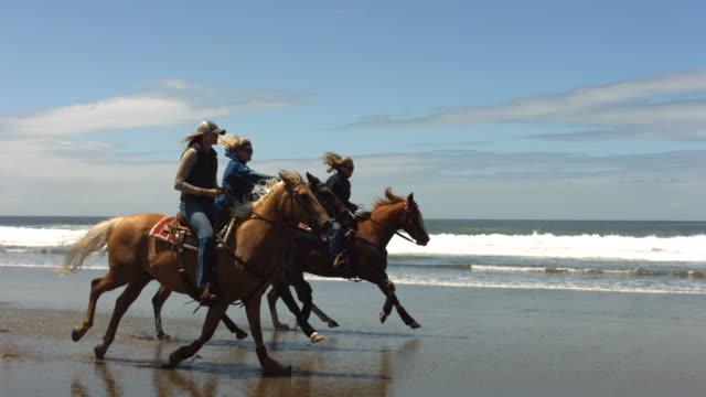 Horseback riding on beach, slow motion video