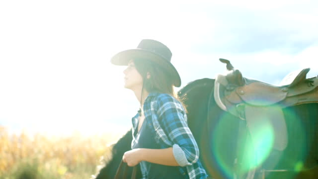 Horses are my passion Beautiful young woman is walking with her horse outdoors in nature , on a sunny day cowgirl stock videos & royalty-free footage