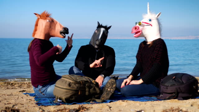 Horses on the beach Three unrecognizable persons wearing horse masks arguing while sitting on the beach near the sea. mask disguise stock videos & royalty-free footage