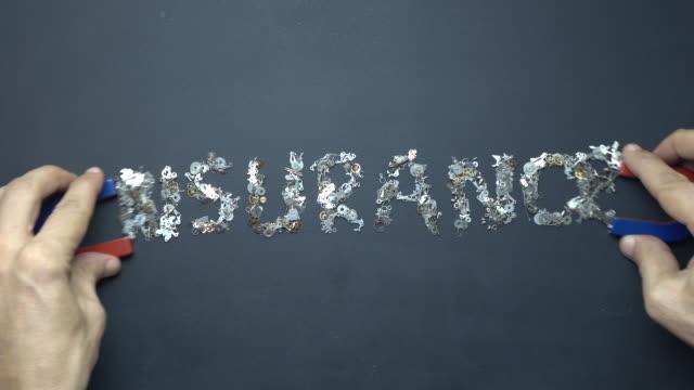 hästsko-magnet i mänsklig hand skrivande ordet försäkring med metall urverk på blackboard - försäkring bildbanksvideor och videomaterial från bakom kulisserna