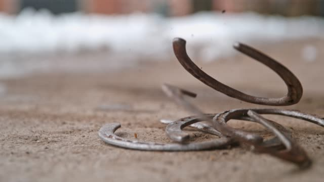 horseshoes falling on ground, super slow motion - horseshoe stock videos & royalty-free footage