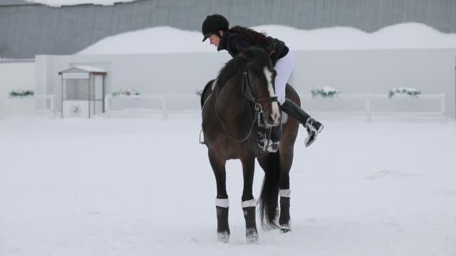 horsewoman climbs up on horseback in a snowy winter day - siodło filmów i materiałów b-roll