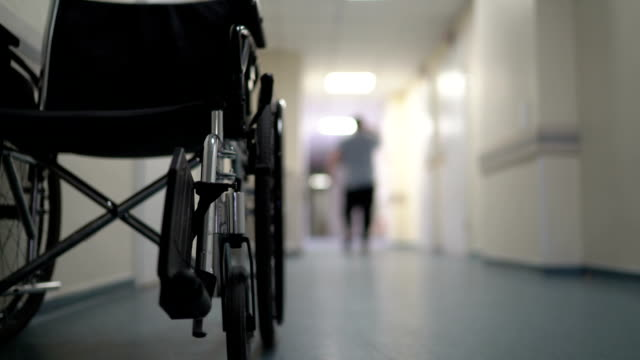 hospital corridor with empty wheelchair and man walking away - senior care stock videos and b-roll footage