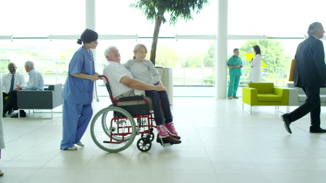 Hospital doctors and nursing staff with patients Assisting people when life throws unexpected obstacles in your way. A hospital ward or waiting area where patients can by seen by doctors and nursing staff. crutch stock videos & royalty-free footage