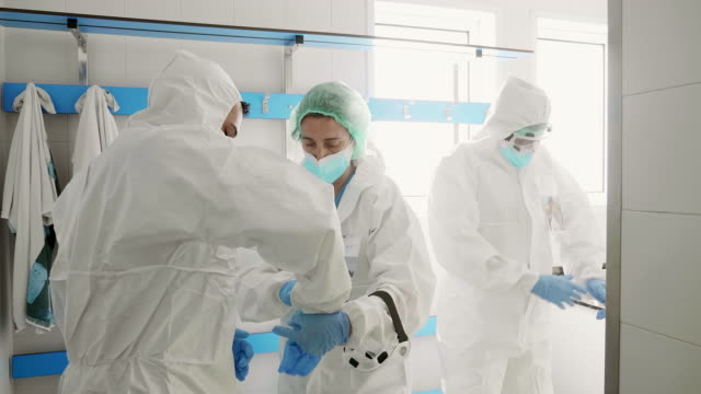 Hospital medical colleagues helping each other with protective gloves equipment at hospital