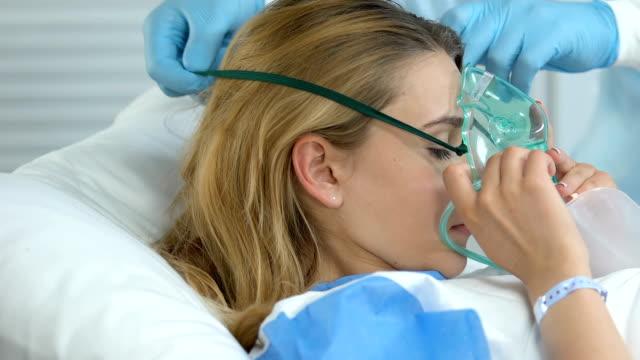 sjukhus sjuksköterska hjälper sjuk kvinna att sätta på syre mask, andningsbesvär - kvinna ventilationssystem bildbanksvideor och videomaterial från bakom kulisserna