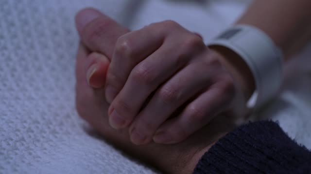 CU Hospital Patient and Visitor Holding Hands Close up of the hand of a female patient lying in a hospital bed, held by the hands of a Caucasian male visitor in low light. nhs stock videos & royalty-free footage