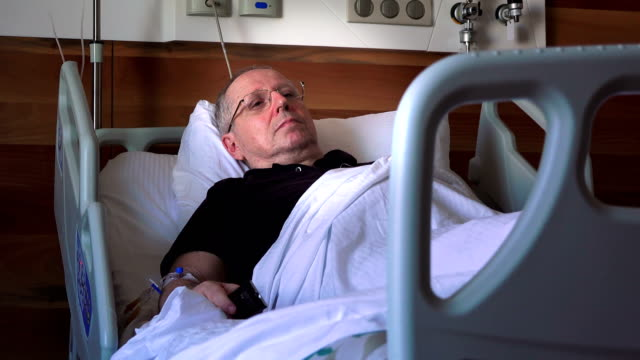 Hospital patient - elderly man lying on a  medical bed - video