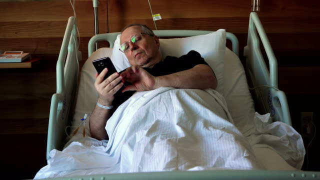 Hospital patient - elderly man lying on a special medical  bed with a mobile phone video