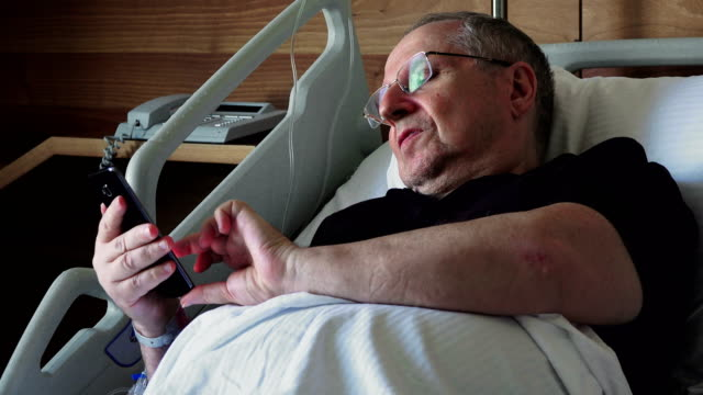 Hospital patient - elderly man lying on a special medical  bed with a mobile phone - video