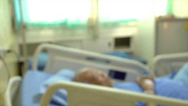panorera sjukhus patientrum med senior patient på säng - intensivvårdsavdelning bildbanksvideor och videomaterial från bakom kulisserna
