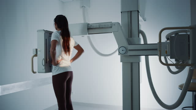 Hospital Radiology Room: Beautiful Multiethnic Woman Standing Next to X-Ray Machine while Female Latin Doctor Adjusts it. Healthy Patient Undergoes Routine Medical Exam Scanning with the Nurse's Help. Hospital Radiology Room: Beautiful Multiethnic Woman Standing Next to X-Ray Machine while Female Latin Doctor Adjusts it. Healthy Patient Undergoes Routine Medical Exam Scanning with the Nurse's Help. mammogram stock videos & royalty-free footage