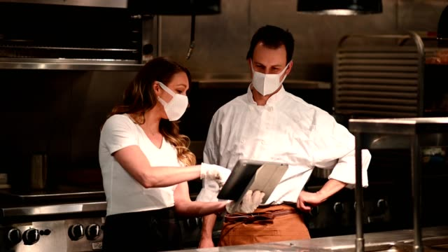 Hospitality team discussing bookings on a tablet Chefs and restaurant manager discussing reservations. Foodservice and hospitality workers. Restaurant staff working. wait staff stock videos & royalty-free footage