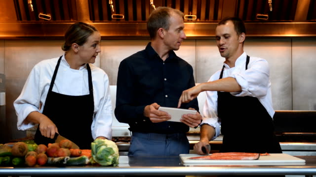 Hospitality team discussing the menu Male and female chefs and restaurant manager quality control stock videos & royalty-free footage