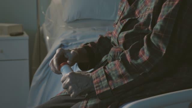 vídeos y material grabado en eventos de stock de hospitalizado hombre mayor sentado en la cama y tomando pastillas - geriatría