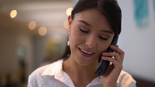 hostess receiving a call for a booking at a restaurant - fare una prenotazione video stock e b–roll