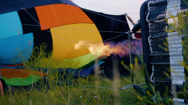 Hot air balloon burner firing and inflates the envelope, slow motion video