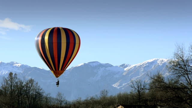hot air balloon in flight over mountains video