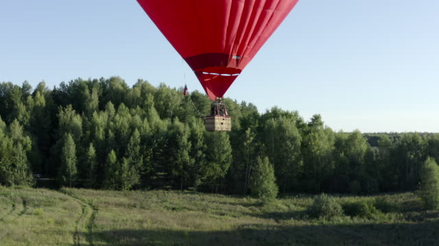 Hot air balloon in heart shape flying over green field and summer forest. Aerostat with basket flying while romantic trip in sky. Red love air balloon aerial view. Hot air balloon in heart shape flying over green field and summer forest. Aerostat with basket flying while romantic trip in sky. Red love air balloon aerial view. hot air balloon stock videos & royalty-free footage