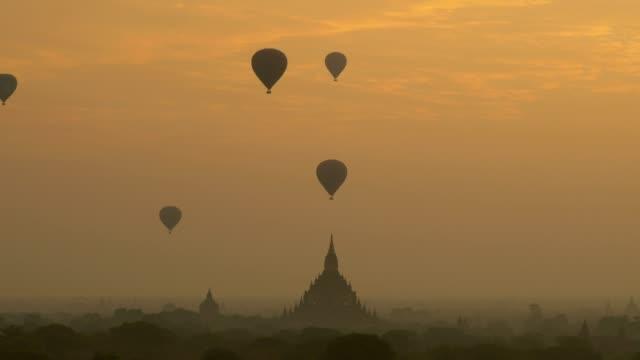 Hot air balloon over plain of Bagan at sunrise, Myanmar Hot air balloon over plain of Bagan at sunrise, Myanmar bagan stock videos & royalty-free footage