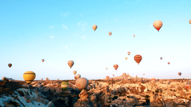Hot air balloons flying over the fairy chimneys with background Uchisar Castle at Cappadocia video