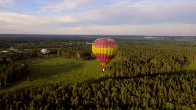 Hot air balloons in the sky over a field.Aerial view video